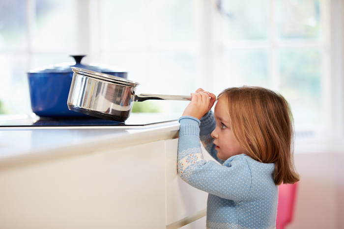 Child reaching for saucepan